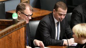 Pääministeri Juha Sipilä (vas), valtiovarainministeri Petteri Orpo sekä perhe- ja peruspalveluministeri Annika Saarikko eduskunnan täysistunnossa Helsingissä keskiviikkona 13. joulukuuta