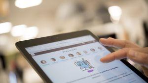 Nainen tutkii Ylen vaalikonetta iPadilla.