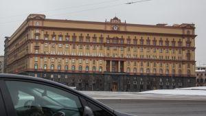 Suuri keltainen rakennus aukion laidalla. Taivas on harmaa.