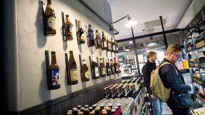 Kaksi miestä katselevat olut valikoimaa Alkossa.