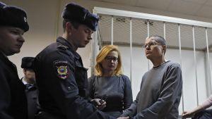 Poliisi laittaa käsirautoja harmaapaitaisen, silmälasipäisen Uljukajevin ranteisiin. Vieressä seisoo Uljukajevin vaimo. Taustalla on häkki, jossa syytetyt istuvan oikeudenkäynnin aikana.