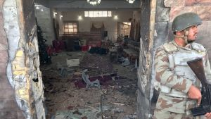 Kuvassa aseistautunut sotilas seisoo kirkon ovella. Taustalla näkyy iskun aiheuttamaa tuhoa.