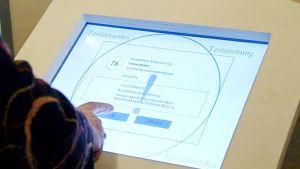 Henkilö käyttämässä sähköistä äänestyslaitetta.