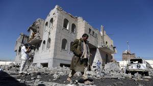 Jemeniläiset tutkivat Saudi-Arabian ilmaiskujen jälkiä Sanaassa 13. joulukuuta. Etualalla kulkee mies pitkässä vihertävänruskeassa päällystakissa kivääri olalta roikkuen. Taustalla mies kuvaa videokameralla maisemaa. Miesten takana on pommituksessa kärsinyt talo. Taivas on kirkkaansininen.