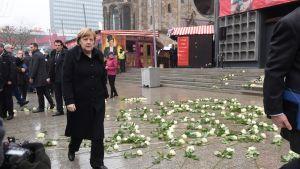 Angela Merkel, taustalla valkoisia ruusuja joulutorilla.
