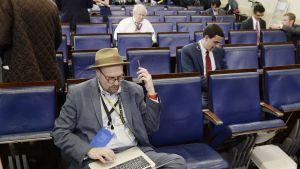Hattupäinen toimittaja Glenn Thrush istuu luentosalissa.