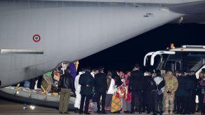 Suuren lentokoneen peräosasta ihmisä tulossa ulos, ihmisiä odottaa ja bussi.