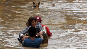 Ihmiset pelastautuivat Tembinin aiheuttamilta tulvatuhoilta Cagayan de Oron kaupungissa Mindanaon saarella Filippiineillä 22. joulukuuta.