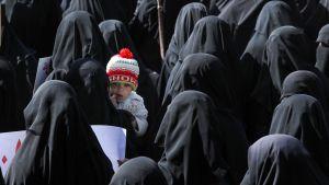 Jemenilänen nainen pitää sylissään lasta mielenilmauksessa YK:n toimistotalon edessä Sanaassa Jemenissä 21. joulukuuta.