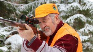 Metsästäjä Pekka Karhu tähtää kiväärillä.