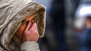 Makedonialainen nainen suojaa kasvojaan saasteiden vaivaamassa Skopjessa joulukuussa 2017.