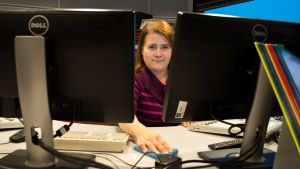 Siivooja Selina Lepistö puhdistaa työpöydän pintoja.