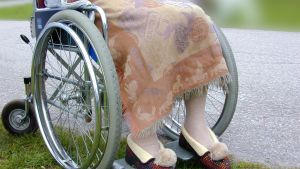 Gammal dam i tofflor sitter i en rullstol