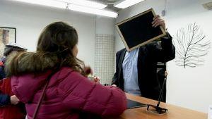Suomen Löytötavarapalvelun työntekijä piiloutuu kameralta
