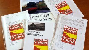 Plastfickor som innehåller namnlistor. Högarna är försedda med ett gulrött klistermärke med texten: Bevara Y-tåget.