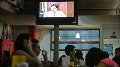 Ihmiset seuraavat Brasilian presidentin Dilma Roussefin televisiopuhetta  kahvilassa. 7b507c4334