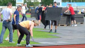 Ungefär 25 personer från fotbollsklubben JBK ser till att gräset täcks med gummimattor.