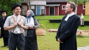 två skådespelare står i gamla kläder med rynkande miner och lyssnar på en gammaldagsklädd präst i pjäsen frihetsdrömmar