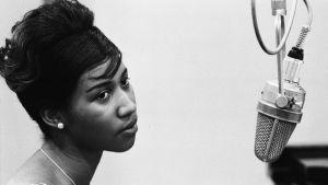Ungdomsporträtt av Aretha Franklin med studiomikrofon