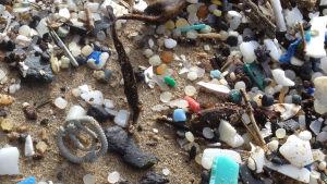 En liten lego-dykarmask bland massvis med plastskräp på en strand.