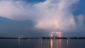 Landskapsbild med vatten i förgrunden, där blixten slår ner i en byggnad långt borta. Bilden är vinnare i kategorin Landskap i tävlingen Årets naturbild 2016.