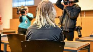 Blond kvinna visar ryggen mot fotografen