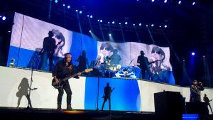 Maffig ljusshow med Finlands flagga i bakgrunden då Scorpions spelar.