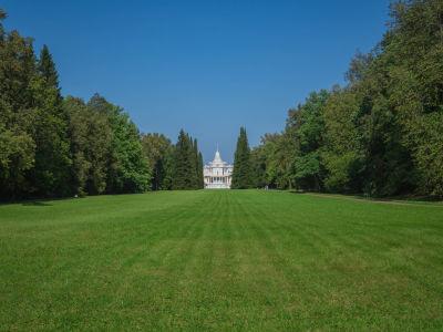 En gräsmatta med en herrgård i bakgrunden.