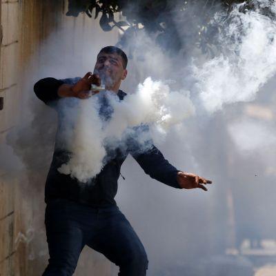 Palestinsk demonstrant i färd med att slänga iväg en gaskanister.