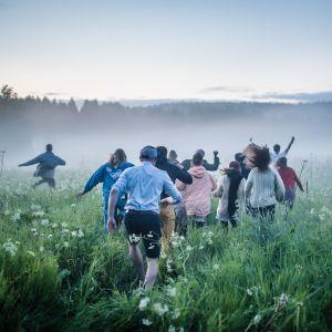 Joukko ihmisiä juoksee poispäin kamerasta vehreällä niityllä. On kesäyö.
