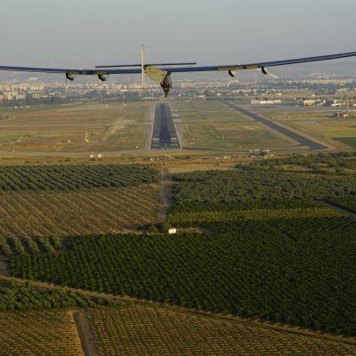 Aurinkolentokone ilmassa peltojen yllä.
