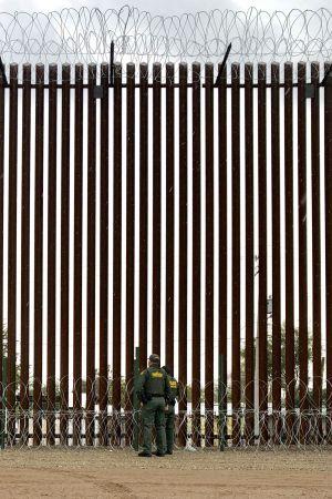 Två poliser ur gränsbevakningen vdi gränsmuren mot Mexiko. Den är fyra gånger högre än de.