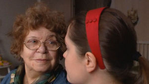 Vanha nainen katsoo nuorta naista ja hymyilee. Kuva kuvanauhalta.