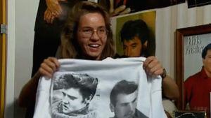 Nainen pitää käsissään Elvis-paitaa. Kuva kuvanauhalta