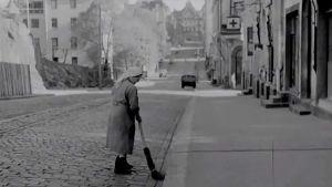 Nainen lakaisee katua Helsingissä.