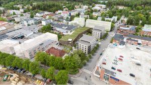 En stad uppifrån med gator, bilar, bostäder och träd.