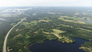 En bild tagen i luften av åkrar, skog och en motorväg.