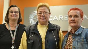 Tre medelålders kvinnor står framför en orange vägg. De tittar in i kameran. På väggen bakom de står det Careeria.