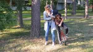 En kvinna stödjer en pojke som försöker åka på en enhjuling i en park.