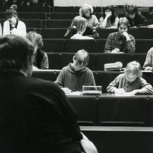 Yläkouluikäisiä tyttöjä ja poikia istuu piirtämässä auditoriossa. Etualalla kasvot yleisöön päin mallina istuva mies.