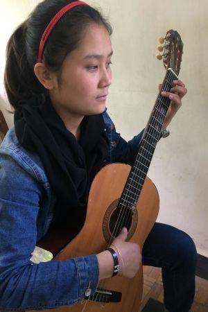 Shukria Fawzi spelar gitarr. Slöjan behövs inte på Afghanistans nationella musikinstitut.