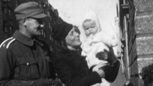 Torsten Korsström och Mirjam Tuominen med Kyra i famnen på en järnvägsstation under andra världskriget.