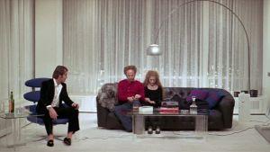 Mies istuu nojatuolissa lasi kädessään, sohvalla mies ja nainen istuvat vierekkäin päät painuksissa. Jack Nicholson, Art Garfunkel ja Carol Kane elokuvassa Miehuusvuodet