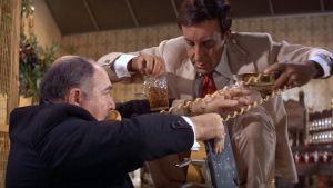 Hrundi V. Bakshi (Peter Sellers) auttaa juhlien isäntää (Stephen Liss) puhelimen johdon kanssa elokuvassa Pahuksenmoiset pirskeet