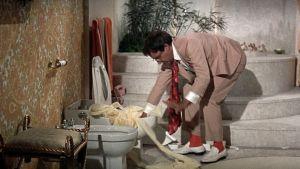 Hrundi V. Bakshi (Peter Sellers) on vaikeuksissa epäkuntoisen vessanpöntön kanssa elokuvassa Pahuksenmoiset pirskeet