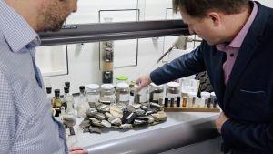 En man visar ett laboratorieskåp fullt med stenar och provrör.