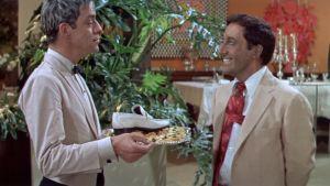 Hrundi V. Bakshi (Peter Sellers) saa kadonneen kenkänsä takaisin alkupalatarjottimella elokuvassa Pahuksenmoiset pirskeet