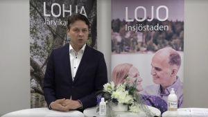 En man i kostym ser in i kameran och talar. I bakgrunden två affischer - den ena med texten Lojo den andra med texten Lohja.