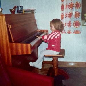 Pieni kolmivuotias tyttö istuu tuolilla pianon ääressä ja tapailee sormillansa koskettimia.