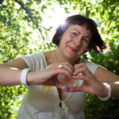 Nainen, joka tekee käsillään sydämen rinnan eteen.